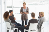 Rehab group listening to woman standing up introducing herself — Stock Photo