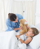 Doctor with teddy bear entertaining  girl — Stock Photo