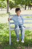 Portrait of a happy boy sitting on bench at park — Foto Stock