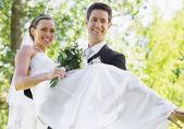 Groom carrying bride in garden — Stock Photo