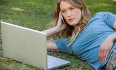 Kvinna med laptop och mobiltelefon i park — Stockfoto