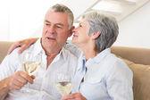 Starszy para siedzi kanapie, picie wina białe — Zdjęcie stockowe
