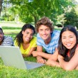 Students with laptop lying on campus — Stock Photo #42930053