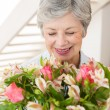 Retired woman holding bouquet of flowers and smiling — Stock Photo #42930161