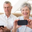 Senior couple sitting on couch using their smartphones — Stock Photo #42930419