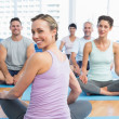 Sporty people sitting on exercise mats at fitness studio — Stock Photo #42931891