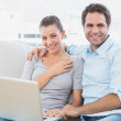 Happy couple sitting on the couch using laptop together — Stock Photo #42932081