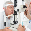 Optometrist doing sight testing for senior patient — Stock Photo #42932279