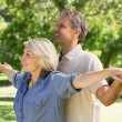 Couple arms outstretched in park — Foto Stock