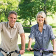 Couple riding bicycles in park — Stock Photo #42932777