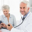 Doctor taking the blood pressure of his retired patient — Stock Photo