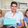 Father holding gifts by children — Stock Photo #42933287