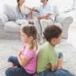 Siblings sitting back to back while parents are arguing — Stock Photo