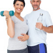 Happy fit couple with dumbbell and water bottle — Stock Photo