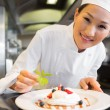 Smiling female chef garnishing food in kitchen — Stock Photo #42933853