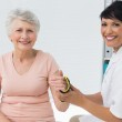 Female doctor fixing wrist brace on senior patients hand — Stock Photo #42934207