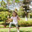 Girl sitting on swing at park — Stock Photo #42934397