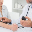 Mid section of doctor taking blood pressure of his patient — Stock Photo