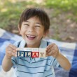 Happy boy holding block alphabets as 'play' at park — Stock Photo #42934479