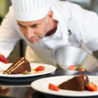 Concentrated male pastry chef decorating dessert — Stock Photo #42934491