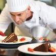 Concentrated male pastry chef decorating dessert — Stock Photo
