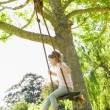 Girl sitting on swing at park — Stock Photo #42934533