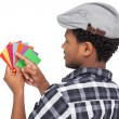 Side view of a young man looking at colorful papers — Stock Photo