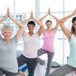 Class standing in tree pose at yoga class — Stock Photo
