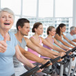 Woman gesturing thumbs up with class at spinning class — Stock Photo #42934909