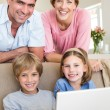Family with laptop in living room — Stock Photo #42934947