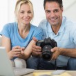 Couple with camera and laptop on sofa — Stock Photo #42935183