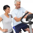 Happy woman looking at mature man on stationary bike — Stock Photo #42935203