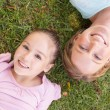 Portrait of mother and daughter lying on grass at park — Stock Photo #42935323