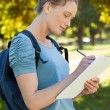Beautiful young woman writing on clipboard at park — Stock Photo #42935495