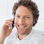 Closeup portrait of a smiling man using mobile phone — Photo
