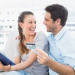 Laughing couple sitting on the couch shopping online with tablet pc — Stock Photo