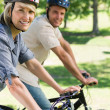 Couple riding bicycles in a park — Stock Photo #42936065