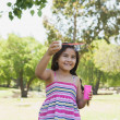 Cheerful girl blowing soap bubbles at park — Stock Photo #42936227