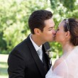 Bride and groom kissing in garden — Stock Photo #42936823