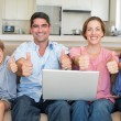 Family with laptop gesturing thumbs up — Stock Photo #42937149