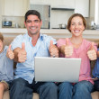 Family with laptop gesturing thumbs up — Stock Photo