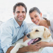 Smiling couple petting their yellow labrador on the couch — Stock Photo #42937211