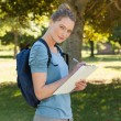 Beautiful young woman writing on clipboard at park — Stock Photo #42937327