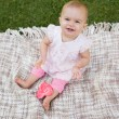 Cute baby with heart shaped lollipop sitting on blanket at park — Stock Photo #42937409