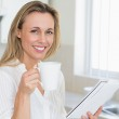 Smiling woman holding mug and newspaper — Stock Photo #42937691