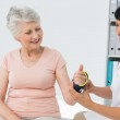 Female doctor fixing wrist brace on senior patients hand — Stock Photo #42937771