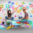 Cheering girl and casual man using laptop with app icons — Stock Photo