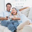 Couple watching funny movie lying on the sofa with bowl of popcorn — Stock Photo