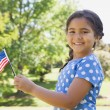 Girl holding the American flag at park — Stockfoto #42937941