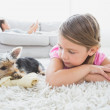 Little girl lying on rug with yorkshire terrier — Stock Photo #42937995
